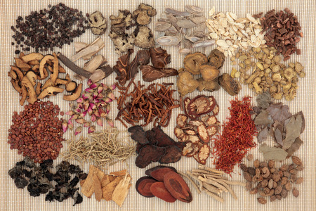 Traditional chinese herbal medicine selection over bamboo background.