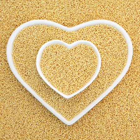 super food: Millet grain super food in heart shaped bowls forming an abstract background. Stock Photo