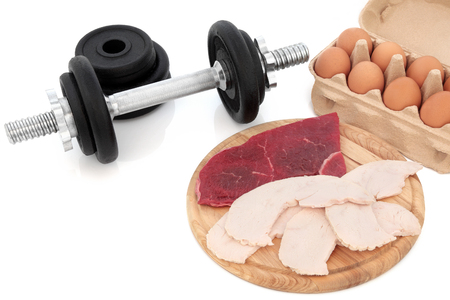 lean out: Dumbbell weights with high protein body building health food of chicken, lean steak and eggs. Stock Photo