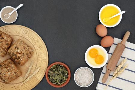 pumpkin seed: Pumpkin seed rolls on a wooden bread board with baking ingredients on slate background. Stock Photo
