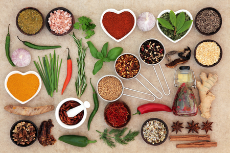 natural selection: Food seasoning with herb and spice selection and chilli olive oil over natural hemp paper background. Stock Photo