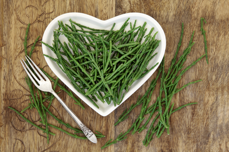 Samphire vegetable health food on a heart shaped china plate and loose over old wood background.