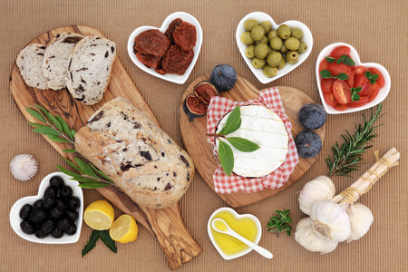 al fresco: Healthy fresh food with olive bread and olives, camembert, fresh and sun dried tomatoes, herbs, garlic, oil and figs. Stock Photo