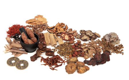 Chinese herb ingredients used in traditional herbal medicine with mortar and pestle and old feng shui coins over white background. 스톡 콘텐츠