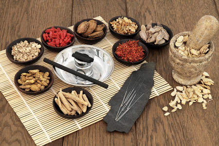 moxibustion: Acupuncture needles, moxa sticks, traditional chinese herbs for herbal medicine and mortar with pestle over bamboo and old oak background. Stock Photo