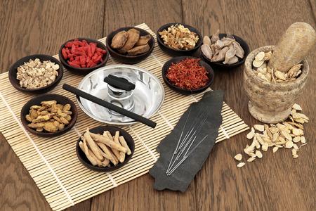 Naalden van de acupunctuur, moxa sticks, traditionele chinese kruiden voor kruidengeneeskunde en mortier met stamper over bamboe en oude eiken achtergrond.
