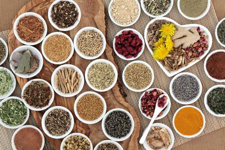 Ampia selezione di erbe usato nella medicina di erbe femminile alternativa su una tavola di legno d'oliva su sfondo di bambù. Archivio Fotografico - 56213222