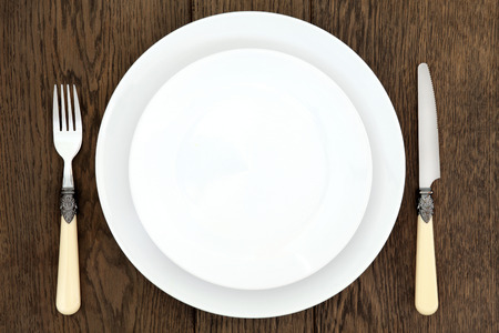 antique dishes: Place setting with white round porcelain dishes, antique cutlery over old oak background. Stock Photo