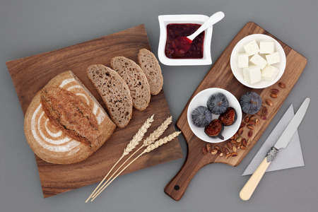 rye bread: Rustic greek snack food with feta cheese, fresh figs, red currant jam, pistachio nuts, rye bread and wheat sheaths on maple board over grey background.