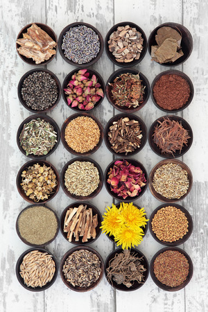 herb medicine: Womens health care herbs in bowls over distressed wooden background.