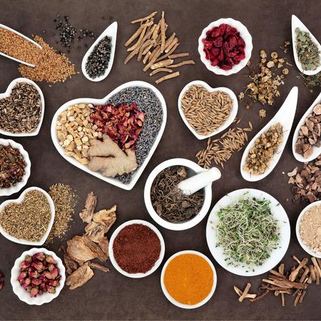 ginseng: Herb selection used in female alternative herbal medicine over lokta paper background.
