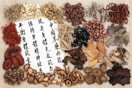 herb medicine: Chinese medicine with herb ingredients and calligraphy on rice paper. Translation reads as chinese herbal medicine as increasing the bodys ability to maintain body and spirit health and balance energy.