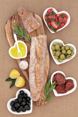 sun dried: French baguette bread on an olive wood board with fresh and sun dried tomatoes, green and black olives and oil in heart shaped bowls with garlic and lemon.