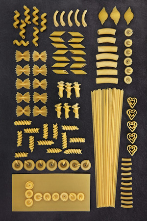 dried food: Large dried pasta food selection forming an abstract background on grey slate. Stock Photo