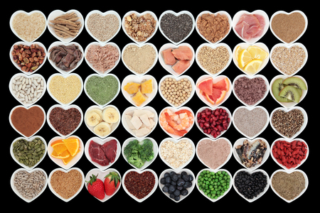 super food: Large health and body building high protein super food in heart shaped bowls with meat, fish, supplement powders, seeds, cereals, grains, fruit and vegetables.