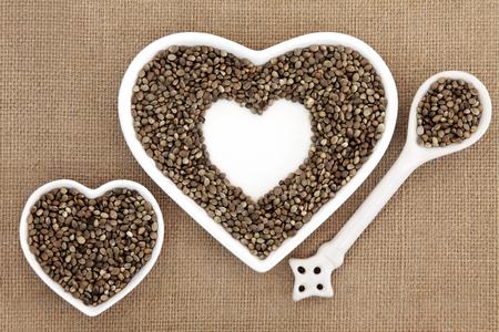 hemp hemp seed: Hemp seed health food in heart shaped porcelain bowls and spoon over hessian background.