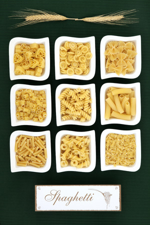 dried food: Italian dried food pasta selection with old wooden sign over ridged green background.