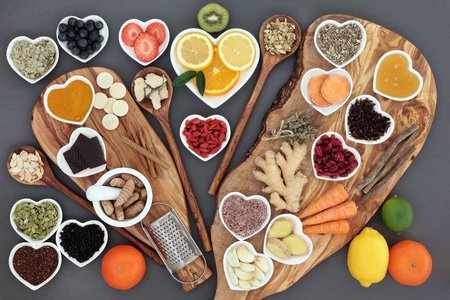 cold cure: Large selection of cold and flu remedy super food and herbal medicine high in antioxidants and vitamin c on olive boards and spoons over grey background..