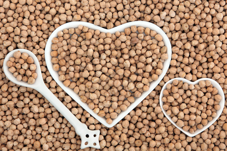 chick pea: Chick pea health food in heart shaped bowls and porcelain spoon forming an abstract background.