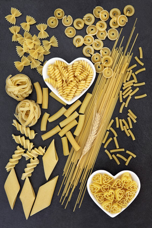 dried food: Dried pasta spaghetti food selection inn heart shaped bowls forming an abstract background over slate. Stock Photo