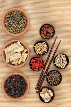 herb medicine: Chinese medicinal herb ingredients used in traditional herbal medicine over bamboo background.