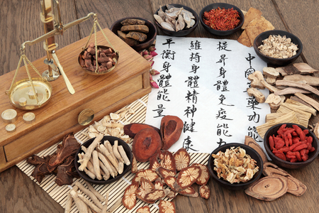 Chinese herbal medicine with herb ingredients, scales and calligraphy on rice paper. Translation reads as chinese herbal medicine as increasing the bodys ability to maintain body and spirit health and balance energy.