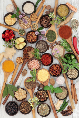 selection: Large herb and spice fresh and dried food selection in wooden bowls and spoons over white distressed wood background.