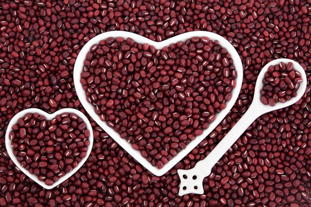 adzuki bean: Adzuki bean health food in heart shaped porcelain dishes and spoon forming an abstract background. Stock Photo