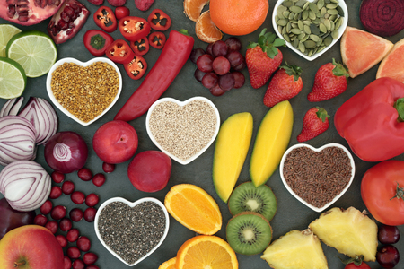 super fruit: Paleo diet health and super food of fruit, vegetables, nuts and seeds in heart shaped bowls on slate background, high in vitamins, anthocyanins, antioxidants, dietary fiber and minerals. Stock Photo