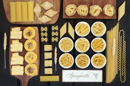 abstract food: Dried italian pasta food selection on maple boards and in porcelain bowls with old spaghetti sign forming an abstract background over dark wood.