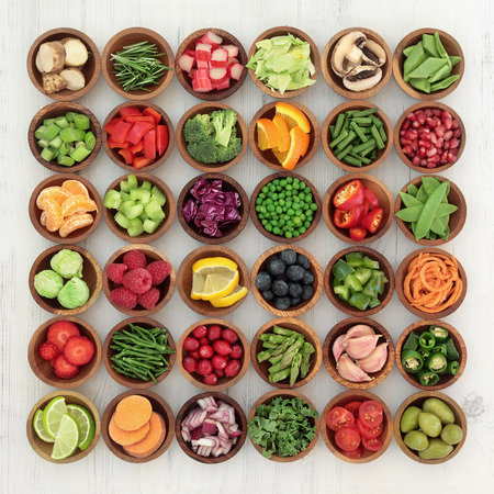 super fruit: Paleolithic super health food of fruit and vegetables in wooden bowls over distressed white wood background. High in vitamins, antioxidants, minerals and anthocyanins. Stock Photo