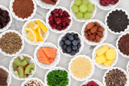 super food: Super food selection in porcelain crinkle bowls over distressed wooden background. High in vitamins, anthocyanins and antioxidants.