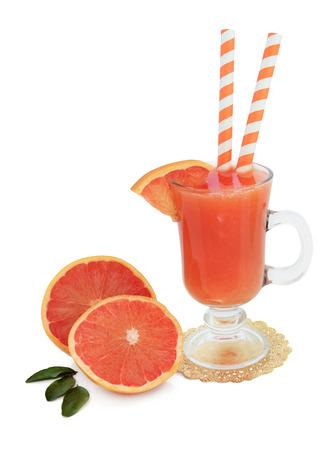 vaso de jugo: Rubí bebida de zumo de pomelo rojo en un vidrio en un Doilie de oro con la paja y frutas frescos de rayas sobre fondo blanco. Alto contenido en vitaminas, antocianinas y antioxidantes.