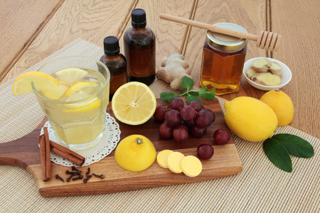 cough medicine: Cold remedies with cough medicine, vitamin c tablets, honey, grapes, spices and hot lemon drink on maple board over bamboo and oak background. Stock Photo