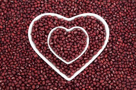 thiamine: Adzuki bean health food in heart shaped porcelain dishes forming an abstract background.