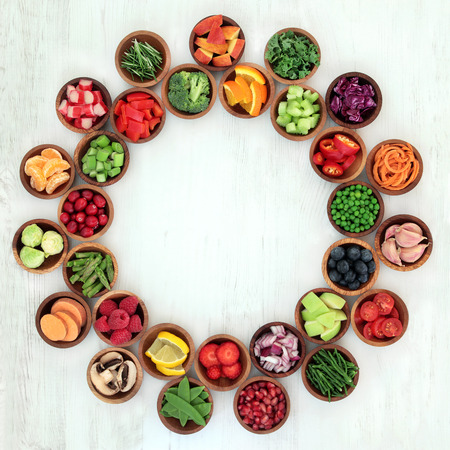 super fruit: Paleo diet health and super food of fruit and vegetables in wooden bowls forming an abstract wheel over distressed white wood background. High in vitamins, antioxidants, minerals and anthocyanins.