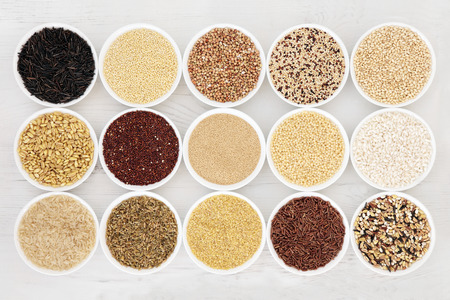 bulgur: Healthy grain food selection in round porcelain bowls over distressed white wood background.