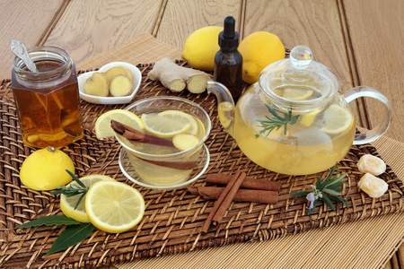 boosting: Honey, lemon, ginger and cinnamon drink for cold and flu relief with glass tea cup and pot, herbs, spices, medicine bottle, cough sweets and fresh fruit on wicker and bamboo mats over oak backgeound. Stock Photo