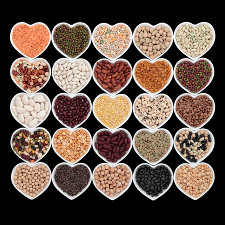 pulses: Vegetable pulses selection in heart shaped porcelain china dishes over black background.