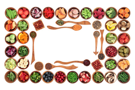 super fruit: Paleo diet health and super food of fruit, herbs, vegetables, nuts and seeds in wooden bowls forming an abstract border over white background. High in vitamins, antioxidants, minerals and anthocyanins. Stock Photo