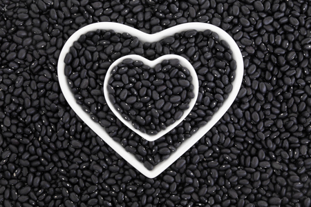 turtle bean: Black turtle bean super health food in porcelain heart dishes forming an abstract background.