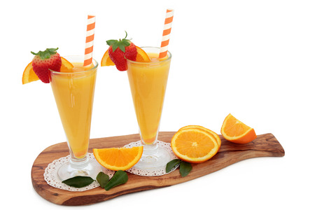 florida citrus: Orange fruit juice drink in glasses with fresh strawberries, striped straws on an olive wood board over white background. High in vitamins, anthocyanins and antioxidants.