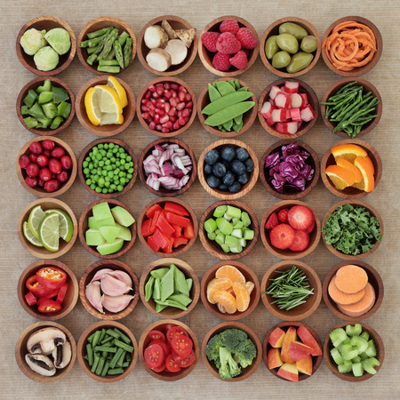 super fruit: Super food sampler for paleolithic diet with fresh vegetables and fruit in wooden bowls over brown paper background. High in vitamins, antioxidants, minerals and anthocyanins.