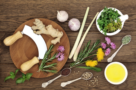 antioxidants: Herb and spice selection with chopper and board, mortar with pestle and olive oil on old oak background.