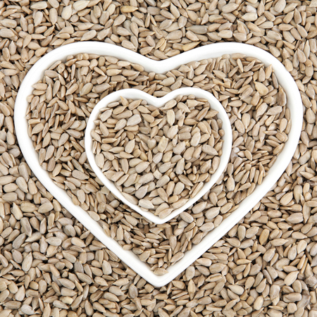 thiamine: Sunflower seed health food in heart shaped porcelain bowls forming an abstract background.