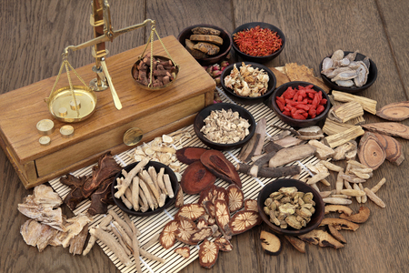 Traditional chinese herb ingredients used in alternative herbal medicine with old brass scales over bamboo and oak background. Stock Photo