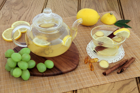 cold remedy: Cold and flu remedy with hot lemon, honey and ginger drink in glass tea cup and teapot, with grapes, spices and  multi vitamin tablets on maple board over bamboo and oak background. Stock Photo