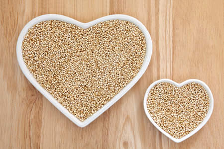 super food: Quinoa grain super food in heart shaped porcelain dishes over beech wood background.