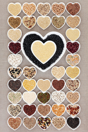 amaranthus: Health food with grain and vegetable pulses in heart shaped bowls over hessian background