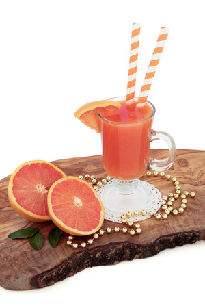 ruby red: Ruby red grapefruit juice drink with fresh fruit, striped straws and gold bead decorations on an olive wood board over white background. High in vitamins, anthocyanins and antioxidants.